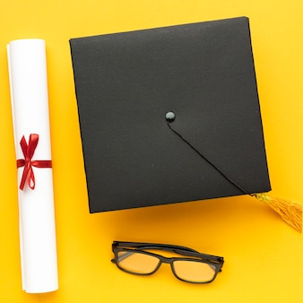 Top view of academic cap with diploma and glasses