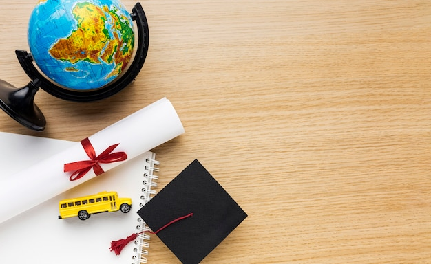 Top view of academic cap with globe and school bus