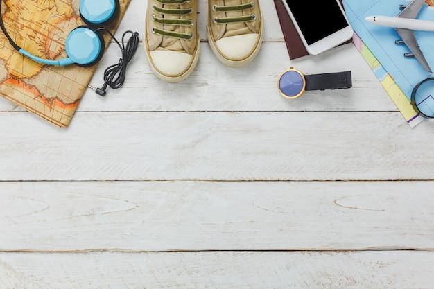 상위 뷰 액세서리 여행 개념 흰색 휴대폰 및 나무 배경에 헤드폰입니다.