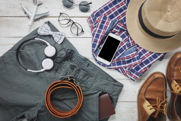 トップビューaccessoires男性服のコンセプトで旅行する。シャツ、ジーンズ、携帯電話、木製の背景上のヘッドホン。パスポート、キー、眼鏡、靴。