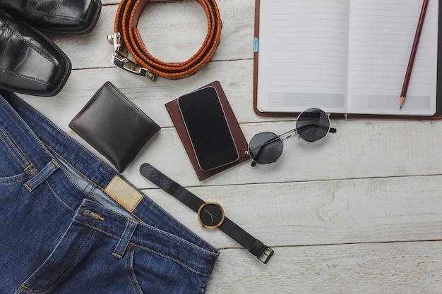 남자 의류 개념 여행 상위 뷰 액세서리. 셔츠, 진, 나무 background.watch, 선글라스와 나무 테이블에 신발에 휴대 전화.