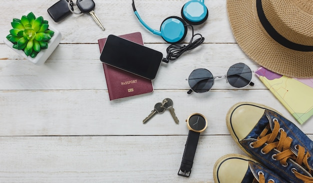 Top view accessoires to travel concept. mobile  phone listening music by headphone on wooden background.shoes,passport,watch,sunglasses and hat on wood table.