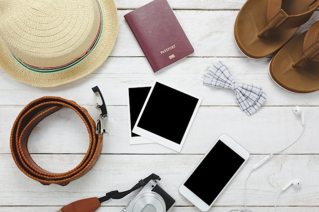 Top view accessoires to travel concept.white mobile phone,hat,passport,camera,photo,sandal on wood table.