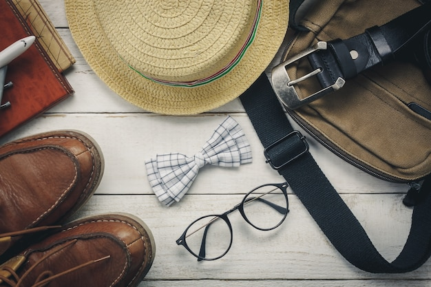 Top view accessoires to travel with man clothing concept. bow tie on wooden background.watch,eyeglasses,bag,hat,airplane,map on white wood table.
