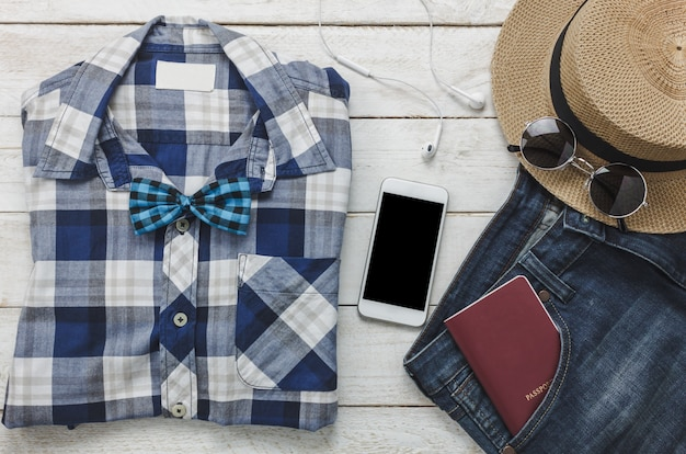 Top view accessoires to travel with man clothing concept. shirt,jean,mobile phone listening music by headphone on wooden background.passport,key,sunglasses and hat on wood table.