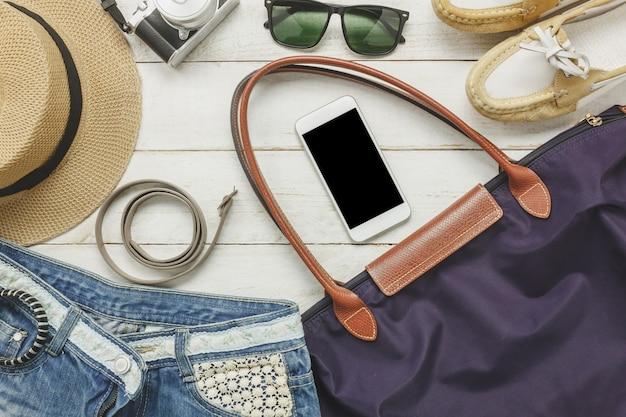 Gli accessori accessibili in alto per viaggiare con le donne vestono il cellulare, la cintura, la borsa, il cappello, la macchina fotografica, la collana, i pantaloni e gli occhiali da sole sul tavolo di legno bianco.