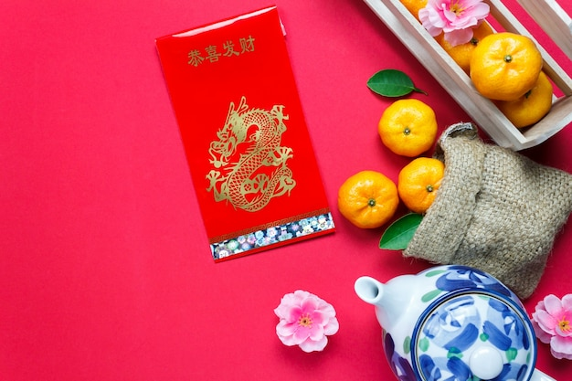 Top view accessories chinese new year festival decorations.orange,leaf,wood basket,red packet,plum blossom,teapot on red background.foreign language means be rich and happy.