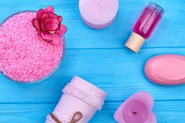 푸른 나무 책상 위에 있는 목욕과 스파용 상위 뷰 액세서리. 비누, 양초, 향수가 든 핑크 히말라야 소금.
