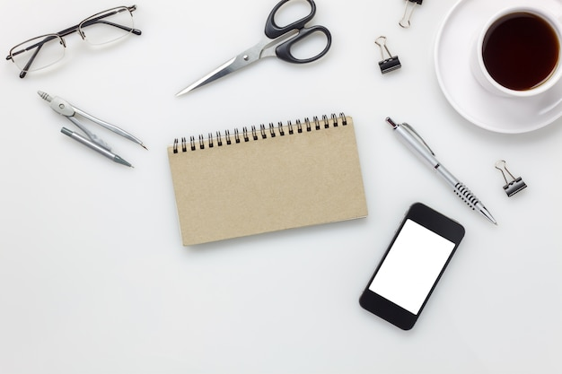 Top view accessories office desk concept.mobile phone,coffee,notepaper,pen,clipboard on white office desk.