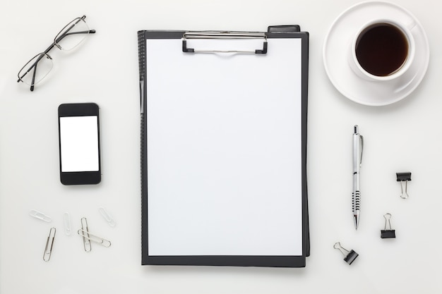 Top view accessories office desk concept.mobile phone,coffee,notepaper,pencil,clipboard on white office desk.