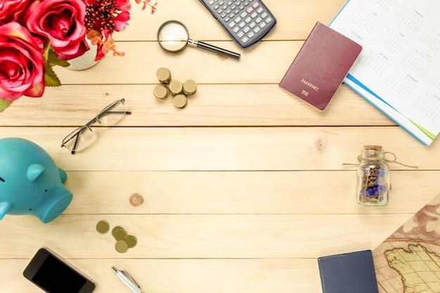 トップビューのアクセサリーは、貯金旅行を貯金箱、パスポート、チャート、カレンダー、花、テーブルのコピースペースで木製に保存します。旅行のコンセプト。