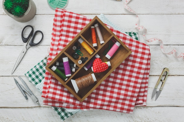 Gli accessori per il fissaggio sono di taglio forbici, bobine di filo, bottoni e abiti da cucire su fondo in legno rustico.