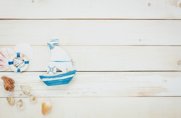 Top view accessories to travel beach.vintage sailboat  with shell on wooden background.