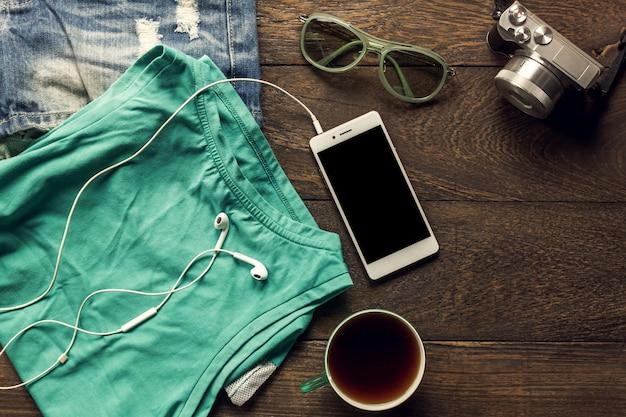 トップビューのアクセサリーは、携帯電話、カメラ、イヤホン、サングラス、布の女性、コピースペースの木製テーブル上のコーヒーで旅行します。旅行のコンセプト。