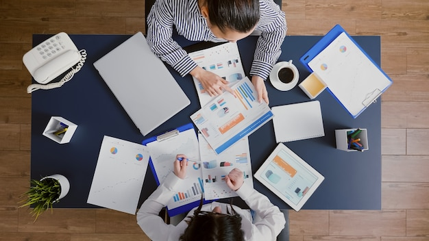 Top view of accountant women analyzing financial graphs paperwork discussing corporate expertise