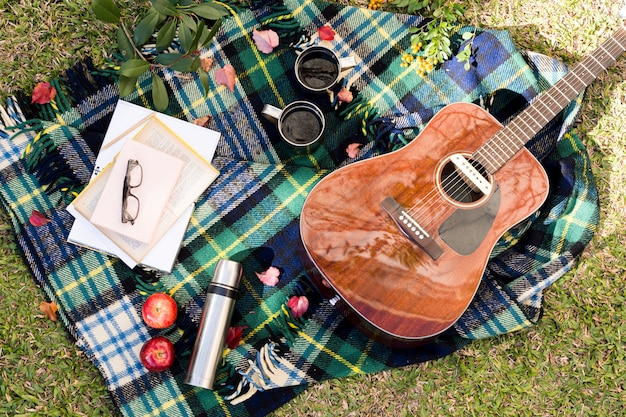 Top view acoustic guitar on picnic cloth