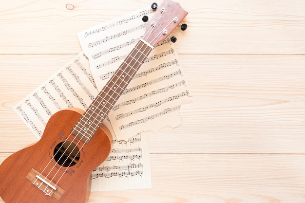 Top view acoustic guitar with wooden background