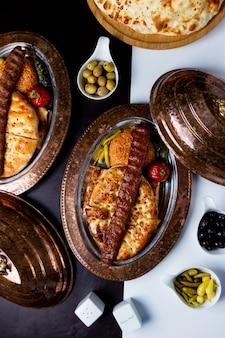 Top view of adana kebab served on tandoor bread and bulgur