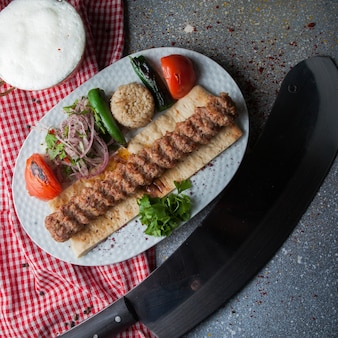 Top view adana kebab with knife and fried vegetables and chopped onion and ayran in white plate