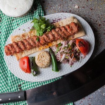 Top view adana kebab with rice and fried vegetables and chopped onion and ayran in white plate