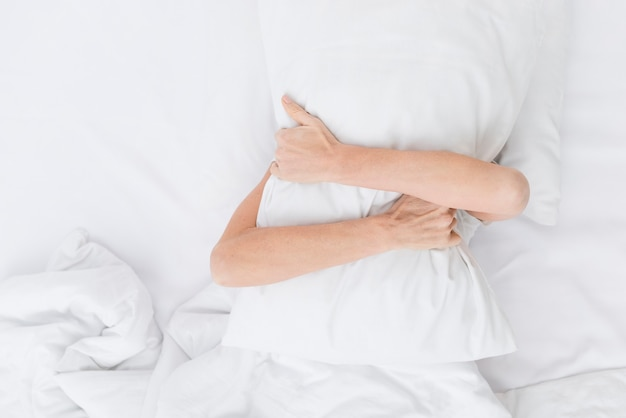 Top view adult woman holding a pillow