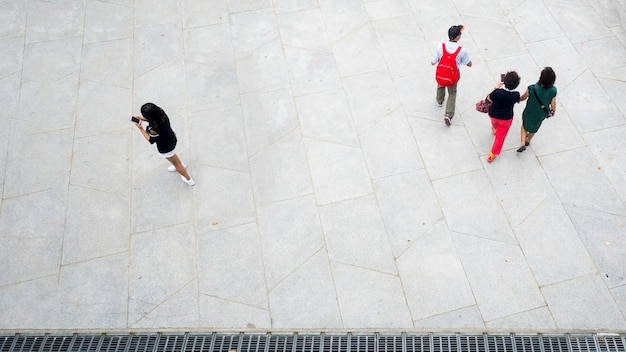 Top view aerial of people walk and use smart phone in pedestrian street