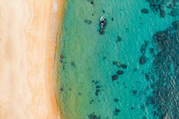 広告テキストメッセージ、プロモーションコンテンツ用のコピースペースを備えたターコイズブルーの水と驚くほど美しい海の風景の飛行ドローンからの平面図の航空写真。完璧なウェブサイトの背景