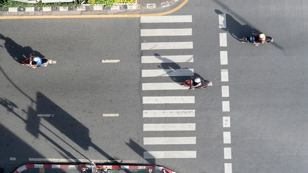 Top view aerial photo of motorcycle driving pass pedestrian crosswalk in traffic road with light and shadow silhouette.