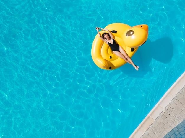 黒の水着でかわいいモデルの平面図の航空写真は膨脹可能なアヒルのプールを楽しんでいます