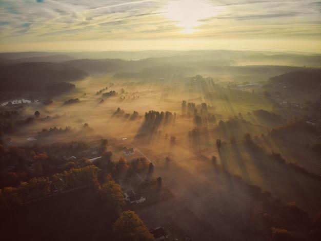 霧のポーランドの村の上から見た空中ショット