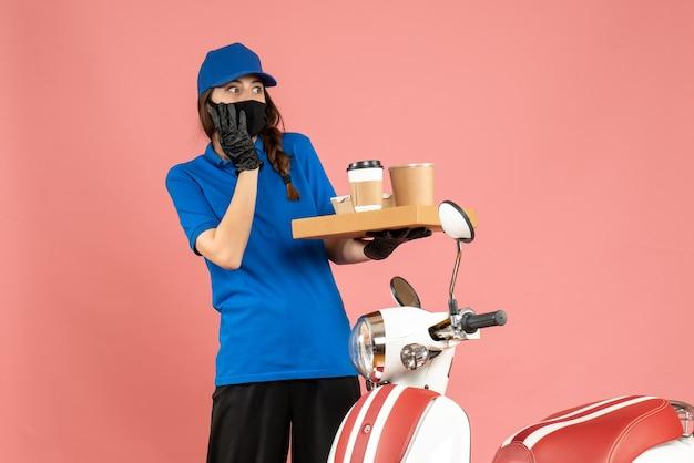 Vista dall'alto della ragazza del corriere impaurita che indossa guanti con maschera medica in piedi accanto alla moto con in mano piccole torte di caffè su sfondo color pesca pastello