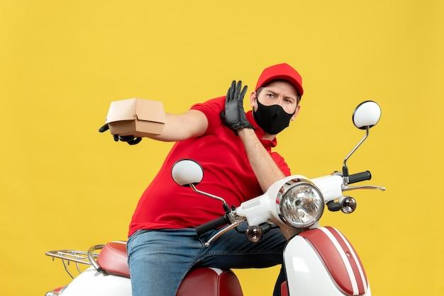 Vista dall'alto del ragazzo delle consegne impaurito che indossa guanti uniformi e cappello in maschera medica che si siede sullo scooter che mostra l'ordine