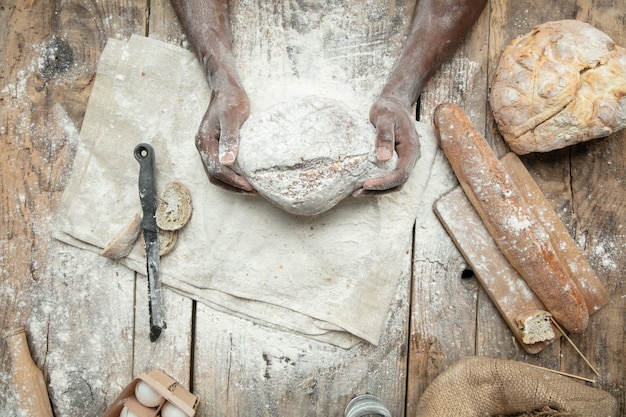 Top view of african-american man cooks fresh cereal, bread, bran on wooden table. tasty eating, nutrition, craft product
