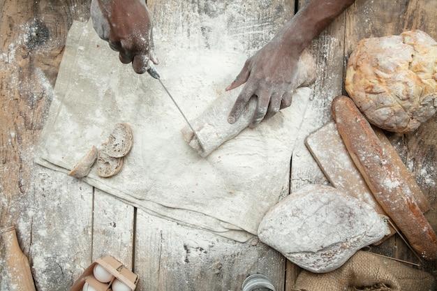 Vista dall'alto dell'uomo afro-americano cuochi cereali freschi, pane, crusca sulla tavola di legno. mangiare gustoso, nutrizione, prodotto artigianale