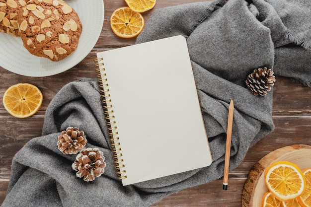 Top view agenda with cookies and pine cones