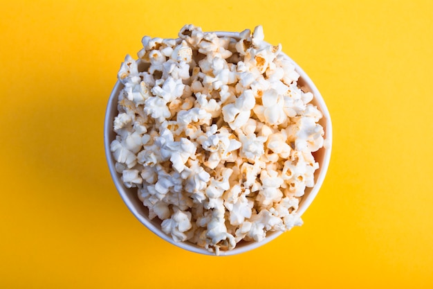 Top view of air tasty popcorn on yellow background
