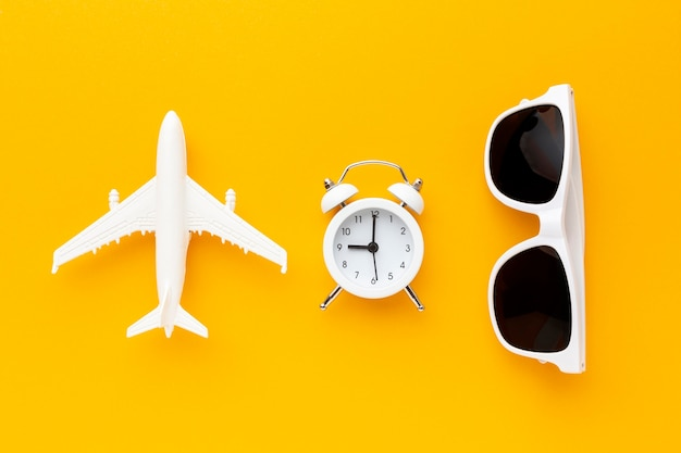 Top view airplane, clock and sunglasses