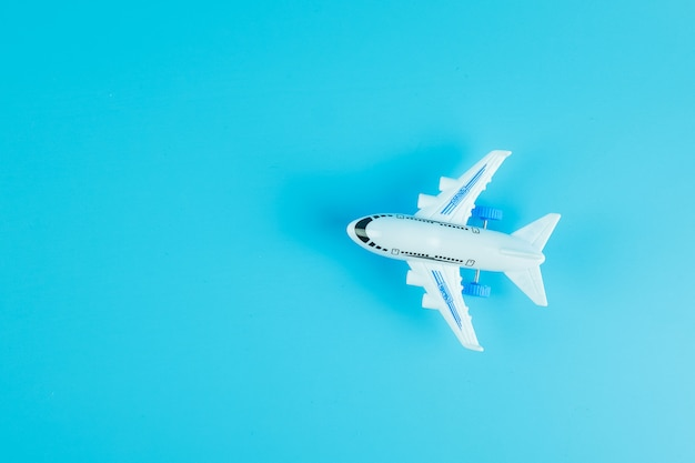 Top view airplane model on blue background with copy space for text