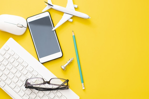 Top view airplane with eyeglasses and smartphone with pencil