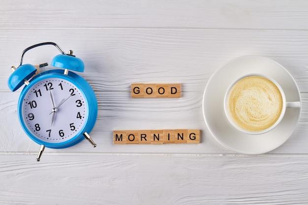 トップビューの目覚まし時計と空のコーヒーカップ。