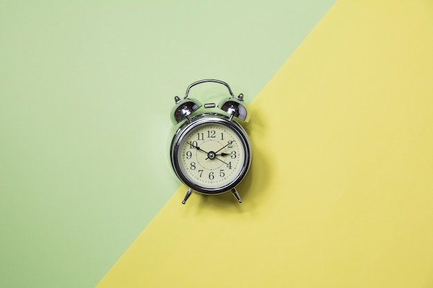 Top view of alarm clock on colorful background and copy space for insert text.