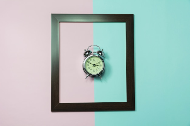 Top view of alarm clock in middle of frame on colorful background