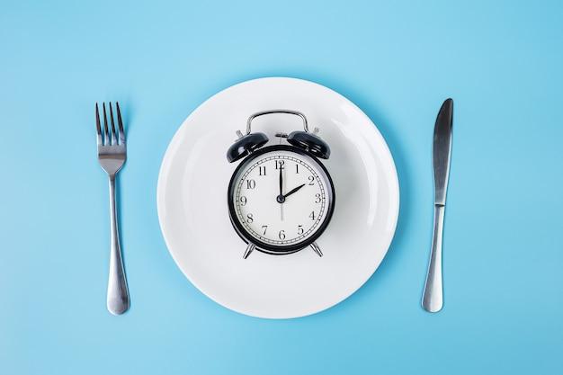 파란색 배경에 나이프와 포크가 있는 흰색 접시에 있는 위쪽 보기 알람 시계. 간헐적 단식, 케토제닉 다이어트, 체중 감량, 식사 계획 및 건강 식품 개념