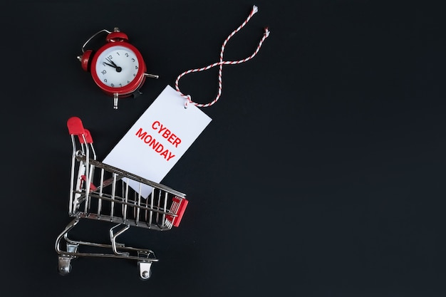 Top view alarm clock and shopping cart with cyber monday sticker on a black . time management, online shopping .