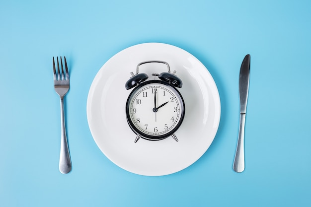 Top view alarm clock on white plate with knife and fork on blue background. intermittent fasting, ketogenic dieting, weight loss, meal plan and healthy food concept