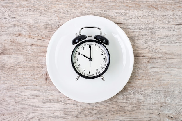 Top view alarm clock on white plate on wooden table background.
