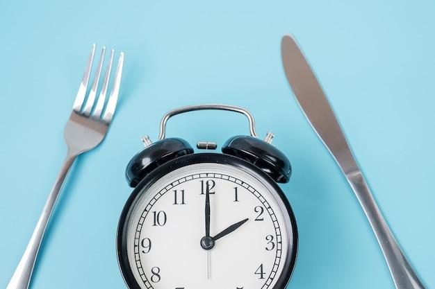 파란색 배경에 나이프와 포크가 있는 상위 뷰 알람 시계. 간헐적 단식, 케토제닉 다이어트, 체중 감량, 식사 계획 및 건강 식품 개념
