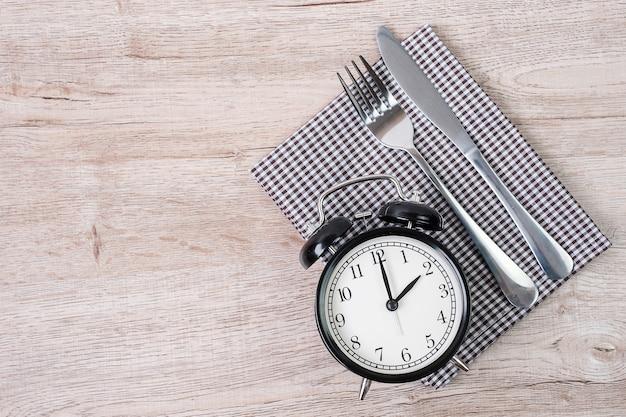 테이블 천 배경에 나이프와 포크가 있는 상위 뷰 알람 시계. 간헐적 단식, 케토제닉 다이어트, 체중 감량, 식사 계획 및 건강 식품 개념