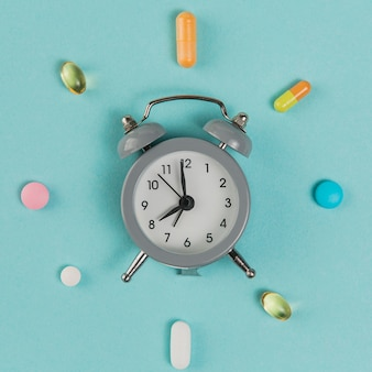 Top view alarm clock with medicine on the table