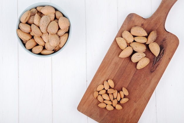 Top view of almond in a bowl and on wooden board on white background